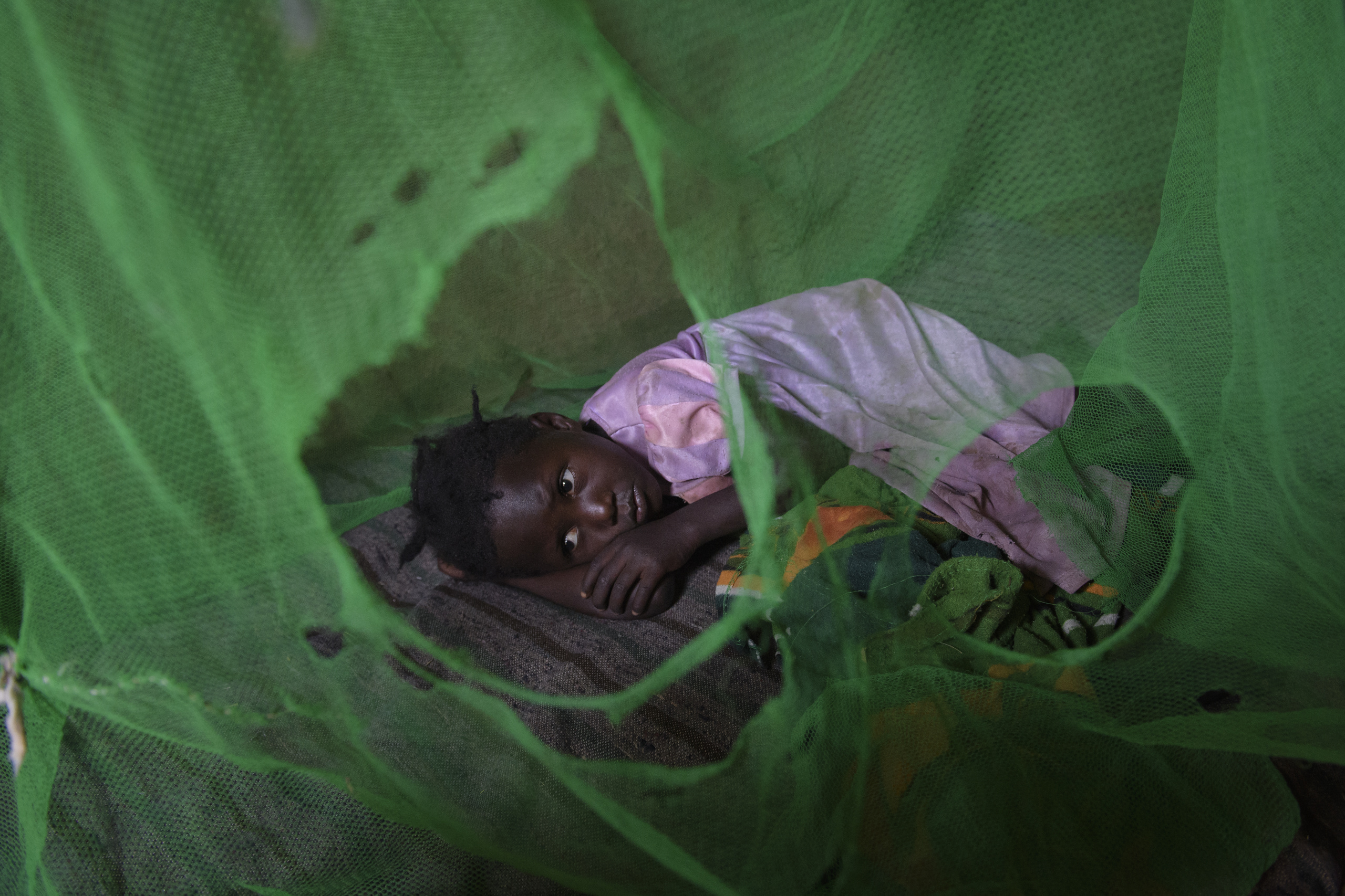 Soroti,UGANDA. A young woman inside is bush house. A lot of people due to the living conditions are affected by malaria.
