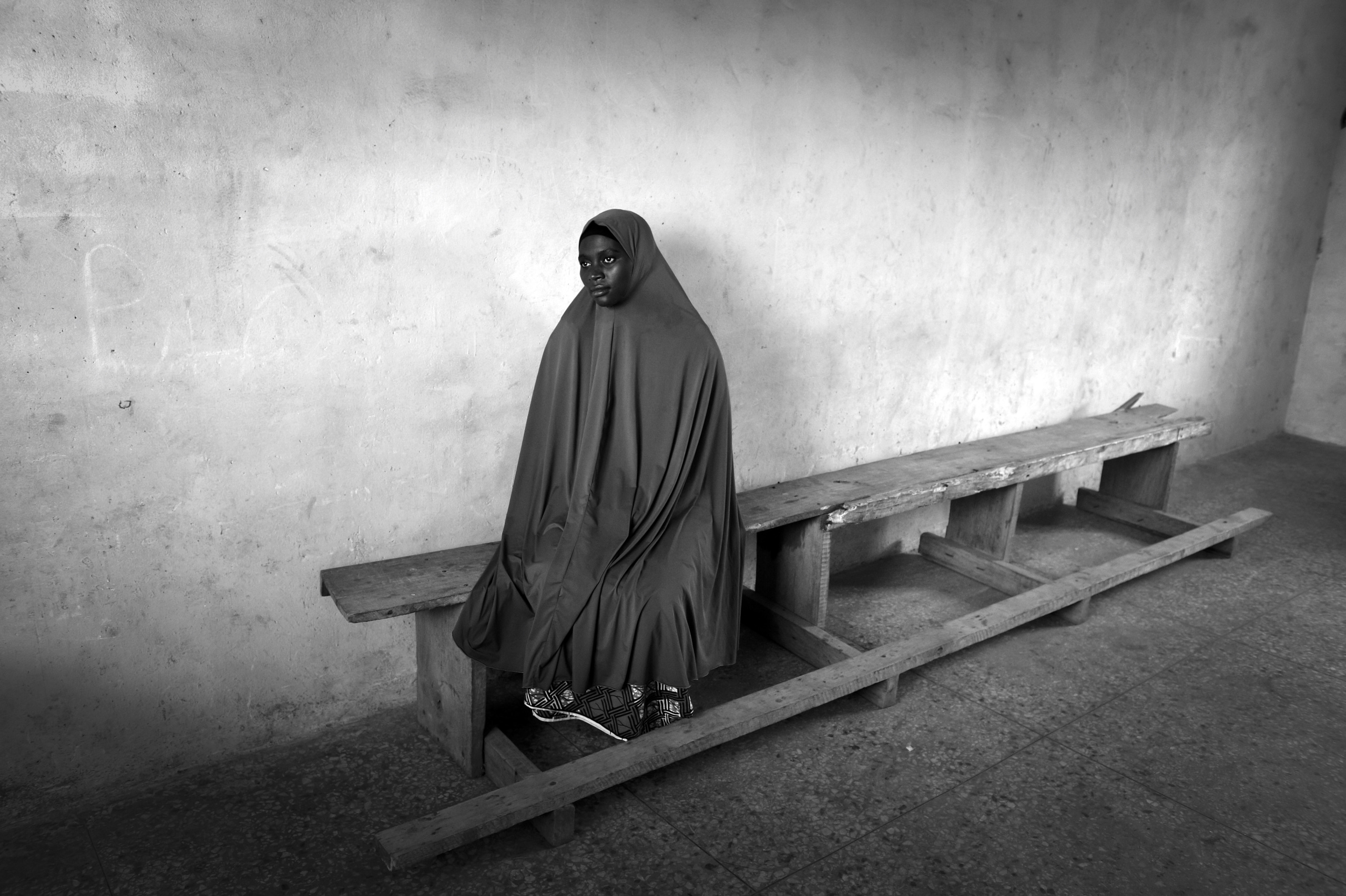 NIGERIA,Kaduna. A Muslim woman waits that her husband picks her up having taken lessons in a Koranic school in a Muslim district of Kaduna. Nearly 4,000 people have died in Nigeria due to the violent conflict over the past decade.  The economic and ethnic conflict in the northern states has a religious dimension. It is only with true governance that these conflicting differences could be managed. As elsewhere in Nigeria, residents accuse both local and state government officials for promoting identity-based divisions to advance their own political agendas. I was commissioned to the City of Kaduna, to expose those individuals who are truly working to make a difference in Nigeria; those individuals who are leading future generations to inspire hope and empowerment of the local communities.