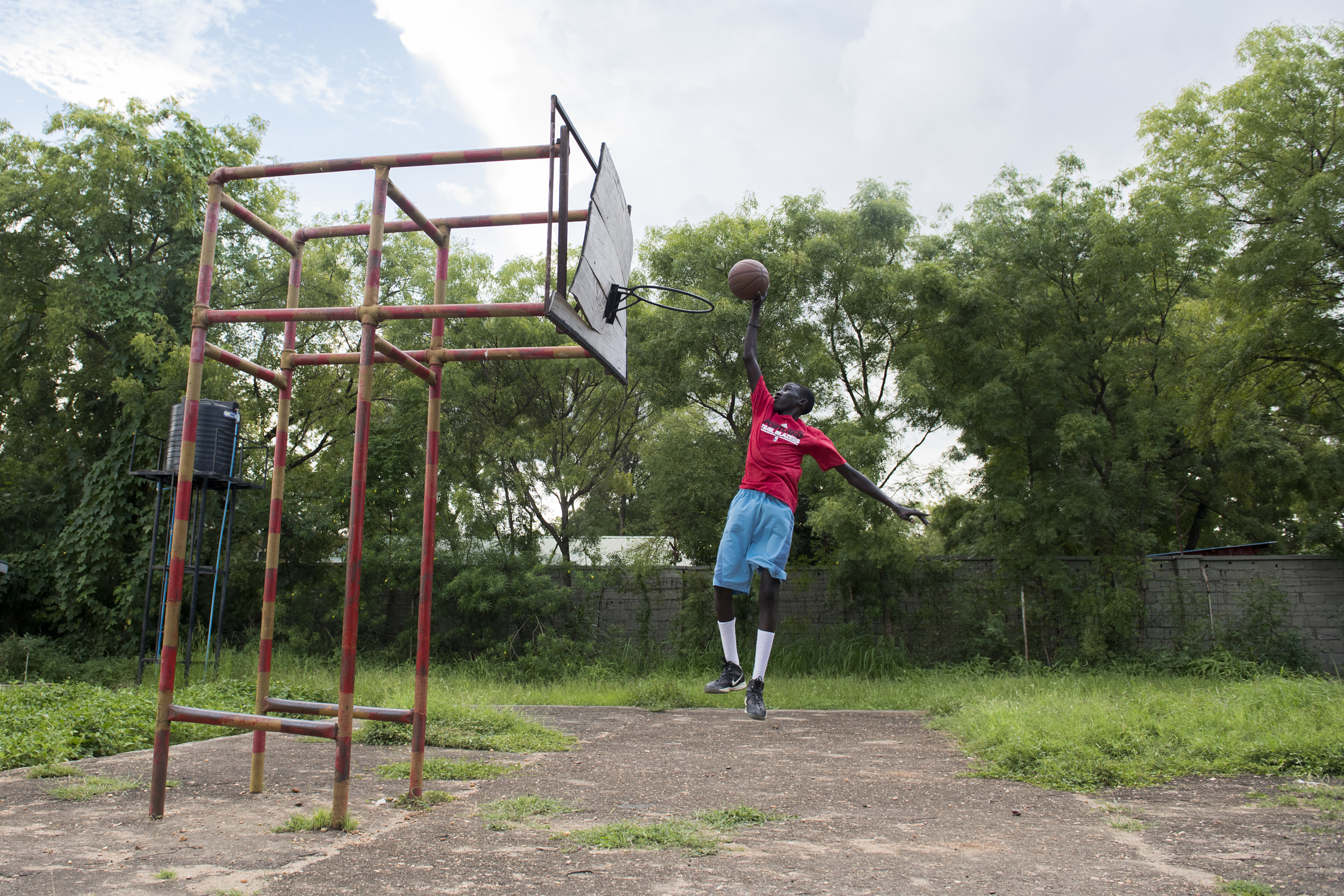 Juba, South Sudan. Young Nuer refugee playing basketball.  The International Basketball Foundation (IBF) was founded in 2008 by FIBA. This Foundation is the social, educational and legacy branch of FIBA ​​to address the role of sport and basketball especially in society. The role of the Foundation is to preserve and promote the values ​​of basketball and its cultural heritage.