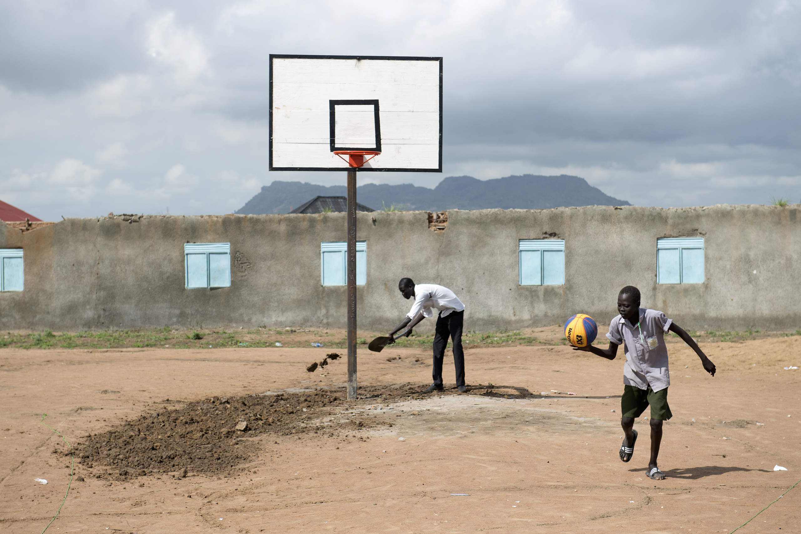 Juba, South Sudan. A man prepare the field for basketball tournament.  The International Basketball Foundation (IBF) was founded in 2008 by FIBA. This Foundation is the social, educational and legacy branch of FIBA ​​to address the role of sport and basketball especially in society. The role of the Foundation is to preserve and promote the values ​​of basketball and its cultural heritage.