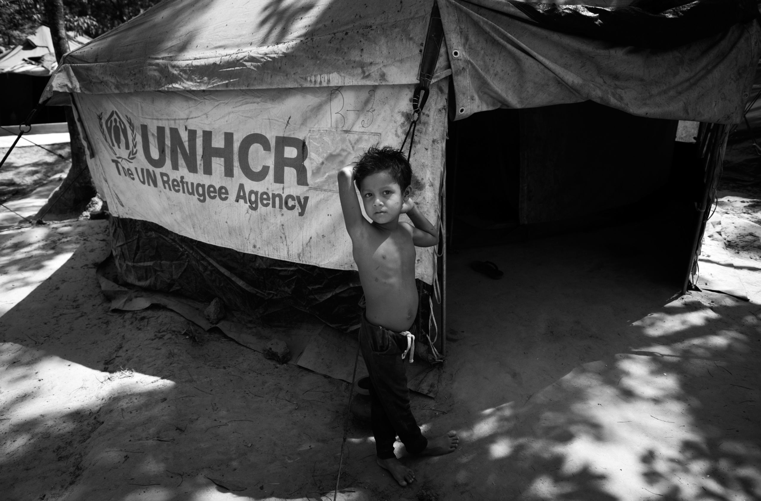 Bangladesh, Cox's Bazaar. Rohingya child poses in front UNHCR tent. Over 650,000 Rohingya have crossed the border to Bangladesh since August last year, fleeing the violence.