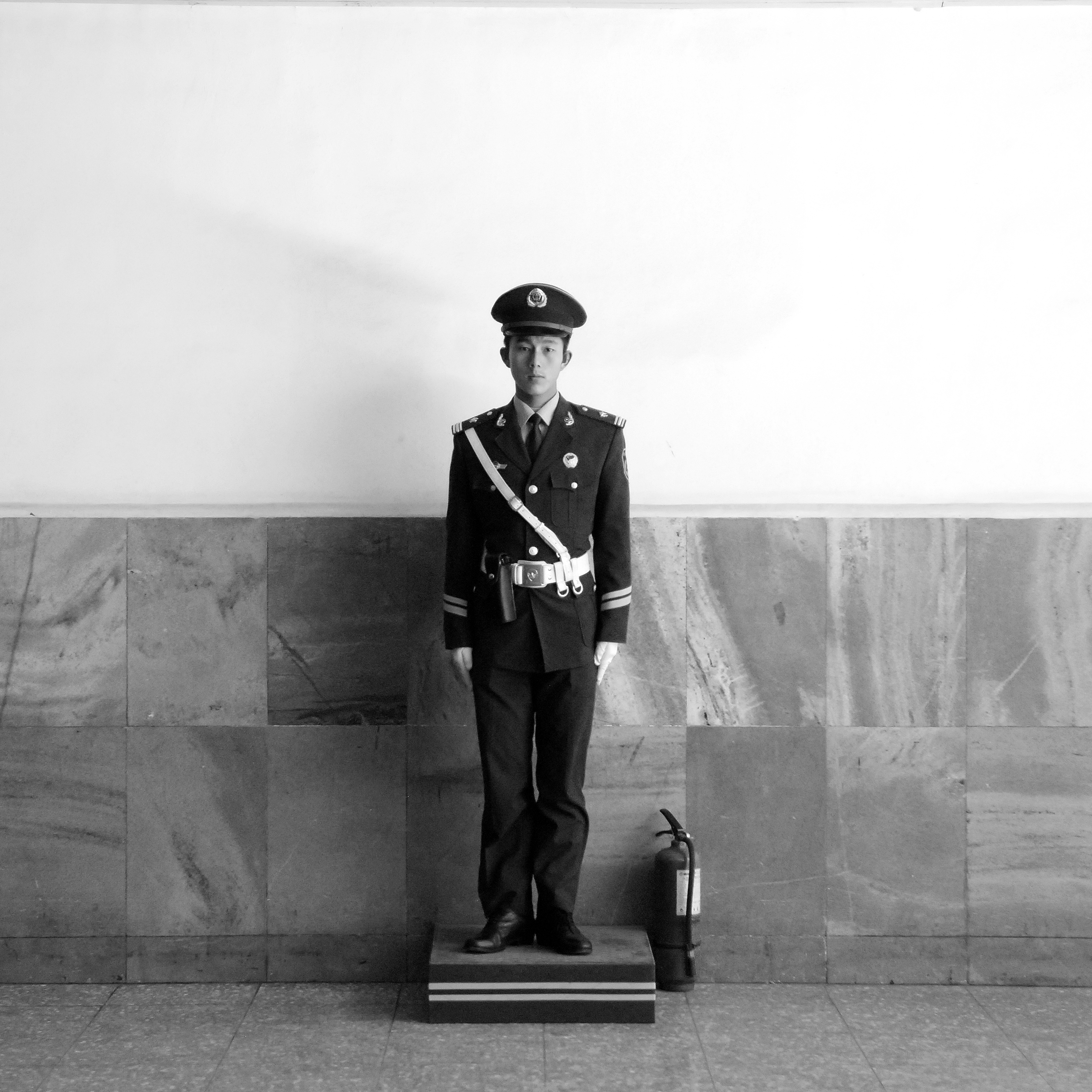 Beijing, China. A policeman guards the subway entrance to Tiananmen Square during the daily sunrise flag-raising ceremony