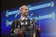 UEFA president Aleksander Ceferin hands over the Champions League trophy ahead of the UEFA football Champion's league semi-finals draw on April 21, 2017 in Nyon. / AFP PHOTO / Richard Juilliart (Photo credit should read RICHARD JUILLIART/AFP/Getty Images)