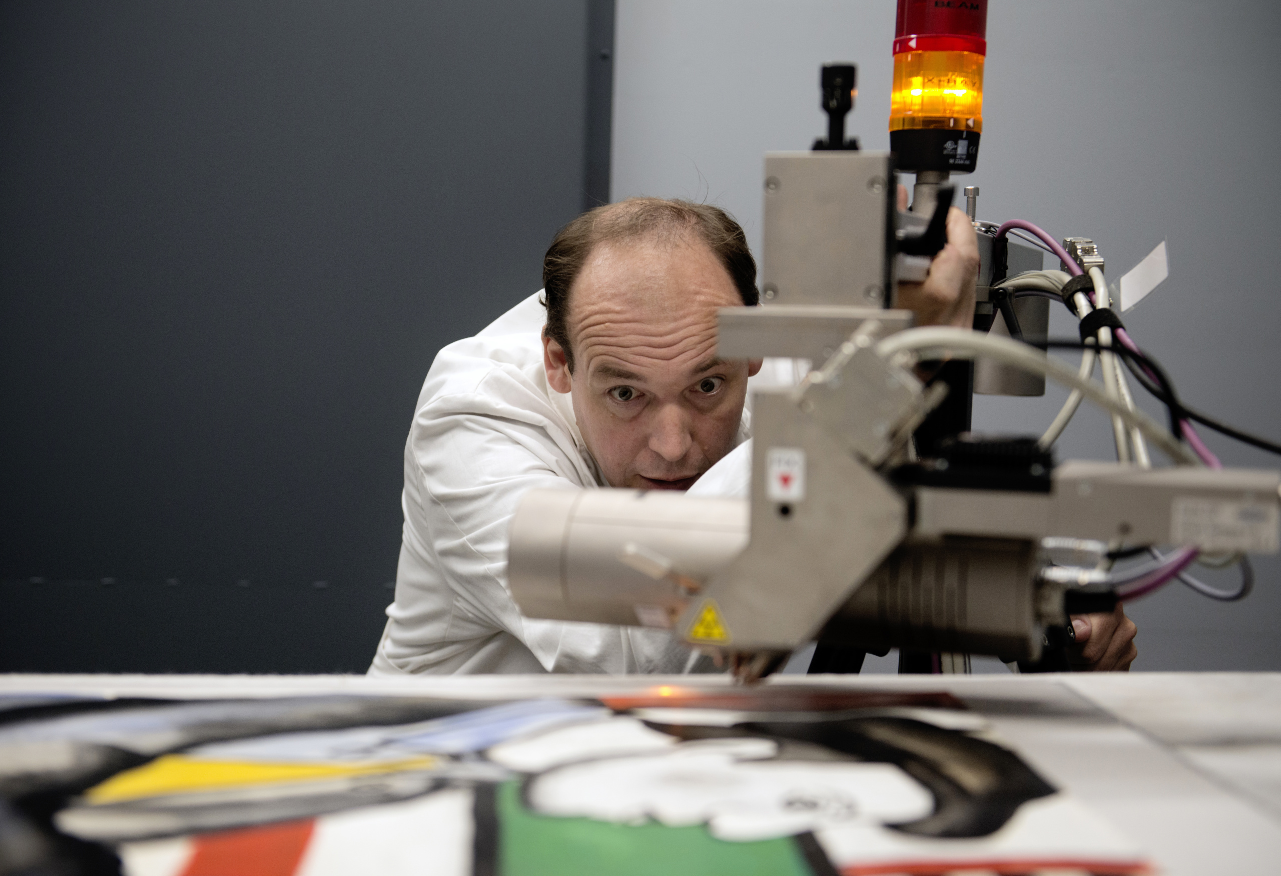 Dr. Killian Anheuser, head scientist at the Fine Arts Experts Institute (FAEI), analyses a bold-coloured painting purportedly by French master Fernand Leger, searching for signs of forgery, on September 19, 2014 in Geneva. AFP PHOTO / RICHARD JUILLIART (Photo credit should read Richard Juilliart/AFP/Getty Images)