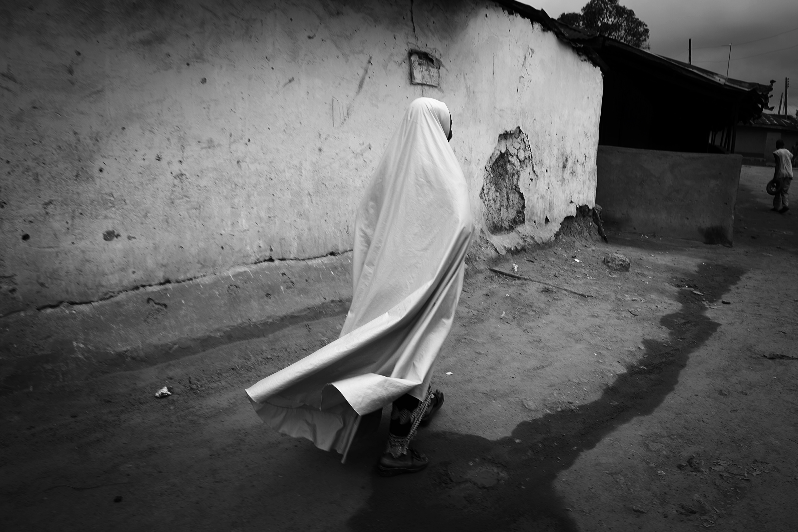 NIGERIA,Kaduna. A woman walks in a street of a Muslim district of kaduna. In the city of Kaduna every community lives in its district. It is rare to find places or Muslim and Christian live together. Nearly 4,000 people have died in Nigeria due to the violent conflict over the past decade. The economic and ethnic conflict in the northern states has a religious dimension. It is only with true governance that these conflicting differences could be managed. As elsewhere in Nigeria, residents accuse both local and state government officials for promoting identity-based divisions to advance their own political agendas.