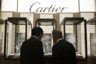 Visitors looks at the stand of Cartier, owned by the Swiss luxury goods group Richemont, during the opening day of the 'Salon International de la Haute Horlogerie' (SIHH), a professional fair in fine watchmaking in Geneva, on January 18, 2016. / AFP / Richard Juilliart (Photo credit should read RICHARD JUILLIART/AFP/Getty Images)