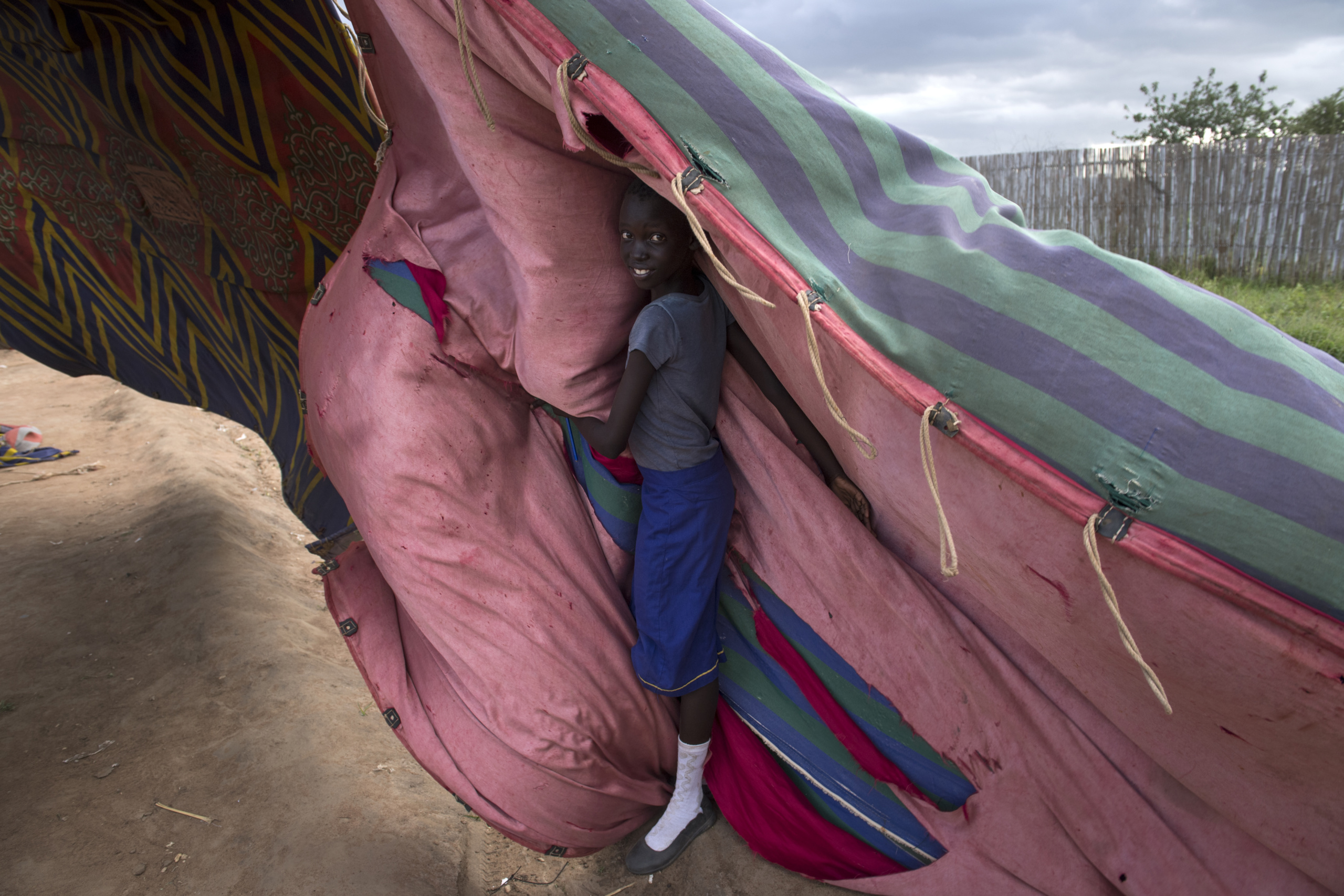 South Sudan, Juba. A woman attempts of protect herself from strong wind .