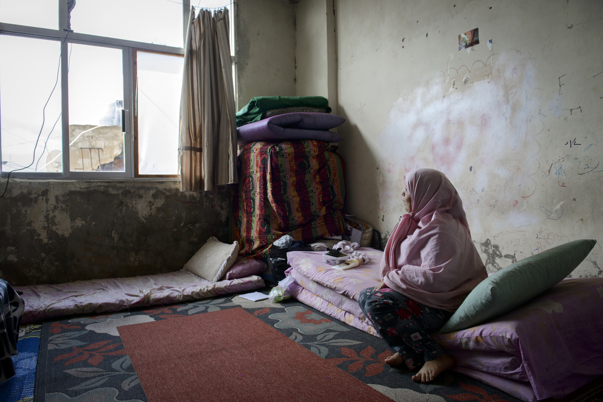 Saida-Lebanon. A woman on his room inside an  abandoned construction site occupied by Syrian refugees.This building is located in the center of Saida . The owner gave access electricity and water free of charge to refugees. . The refugees  try to survive through public subsidies and underpaid labor. the Lebanese government will not allow traditional refugee camps in Lebanon, refugees are finding unusual places to live across the country, including unfinished homes, abandoned shopping malls and schools .......