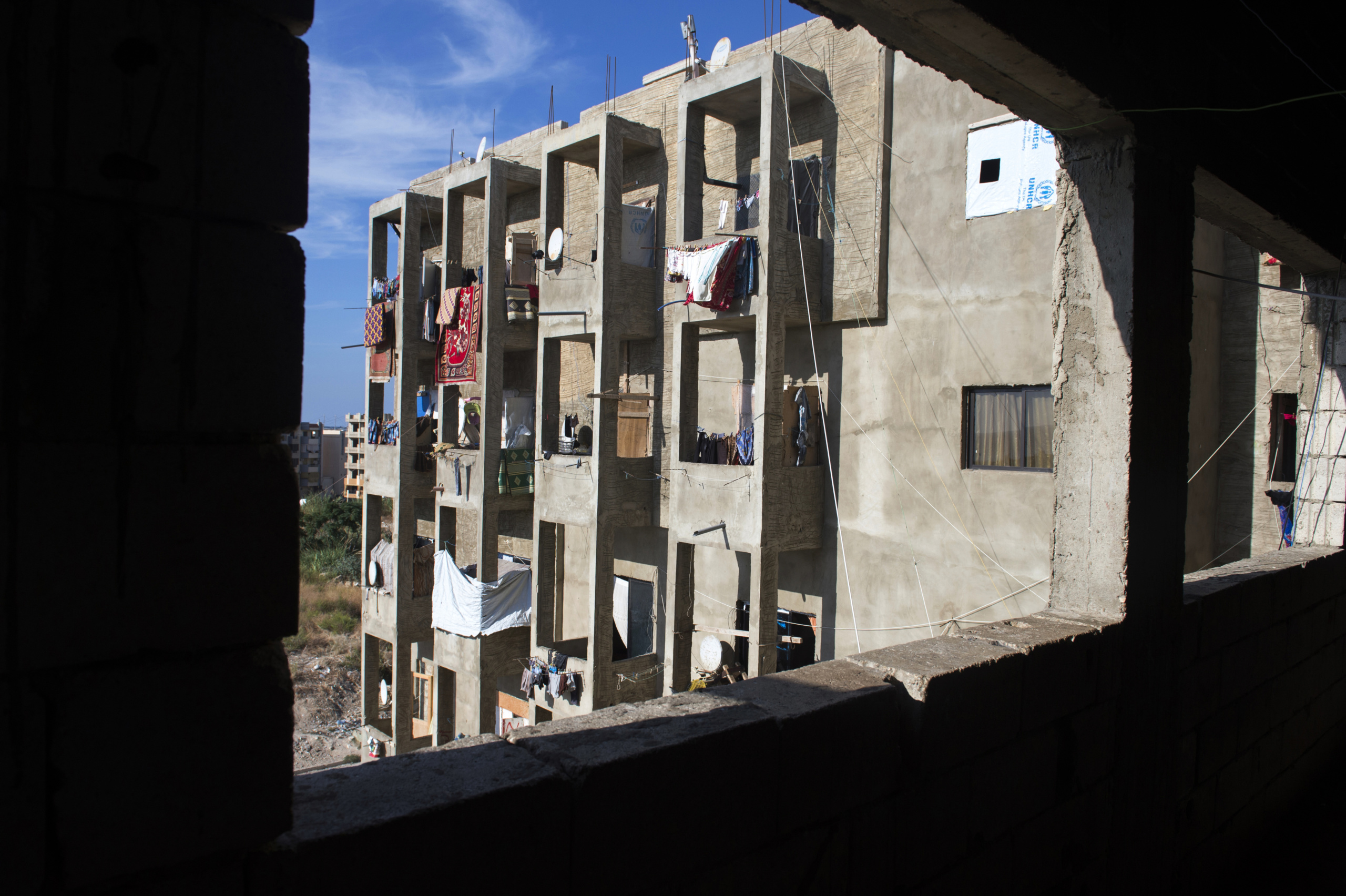 "Saida-Lebanon. An abandoned construction site occupied by Syrian refugees. This building, referred to as a ""collective shelter"", is owned by the Islamic University and financed by a Kuwaiti association. About 150 families live within it, all from the Syrian Daraa region. The refugees try to survive through public subsidies and underpaid labor. the Lebanese government will not allow traditional refugee camps in Lebanon, refugees are finding unusual places to live across the country, including unfinished homes, abandoned shopping malls and schools ……."